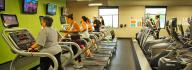 Members using cardio equipment, including treadmills, ellipticals, bikes and stair climbers in the wellness center at the YMCA on Granby