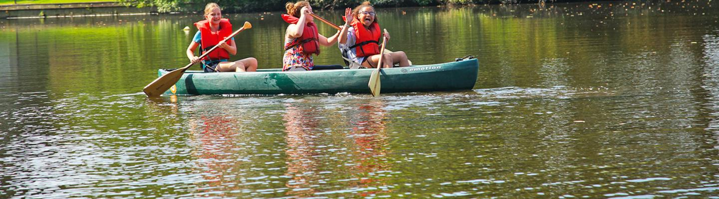 Picture of three girls canoeing in a lake, waving at the camera