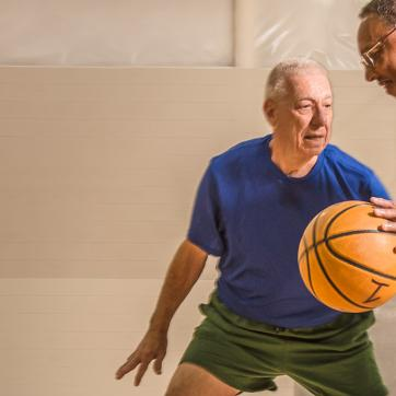 Two older adults playing 1 on 1 basketball