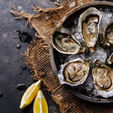Six roasted oysters on ice, with lemons and oyster knife