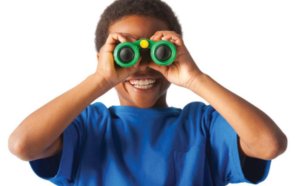 African-American boy smiling and looking at you through binoculars