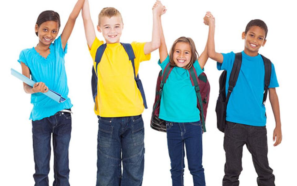 Group of young YMCA childcare participants with backpacks raising held hands together