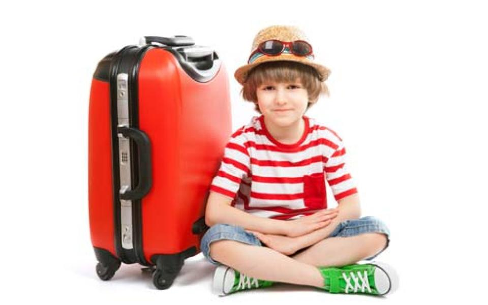 Boy sitting on the ground next to suitcase, ready to go to summer camp