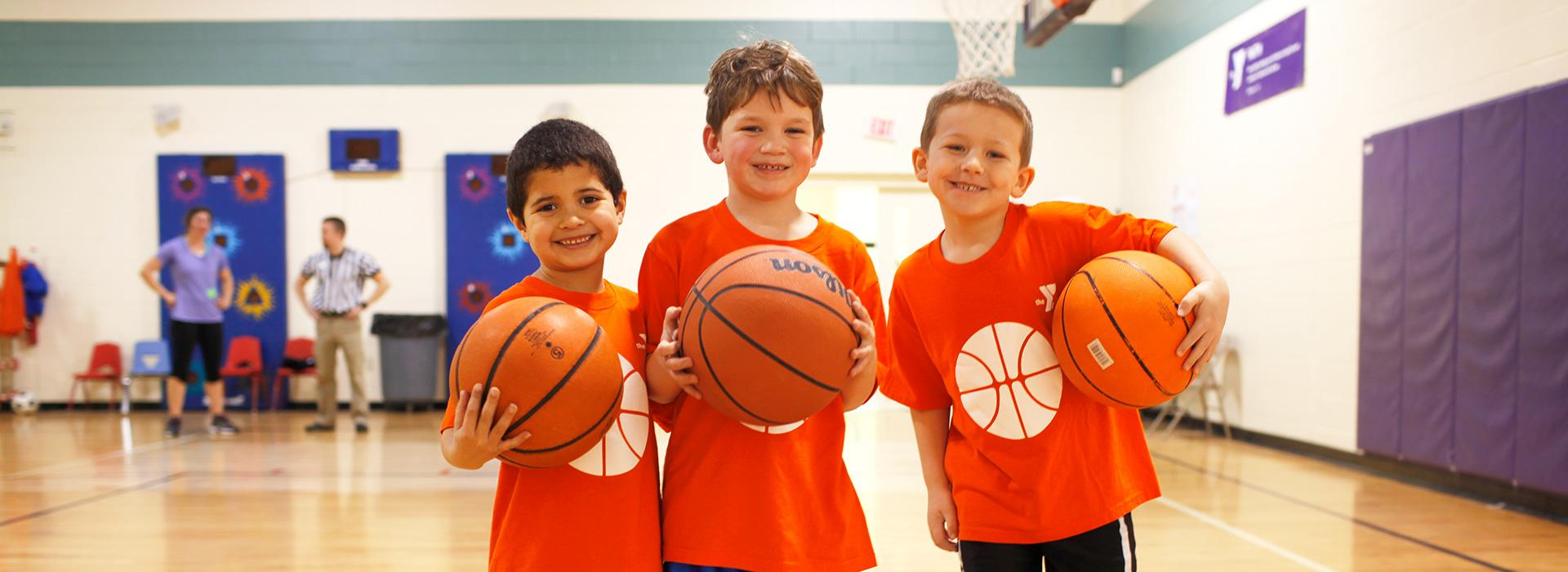 Three young YMCA basketball players holding basketballs in the indoor gymnasium at the Hilltop Family YMCA