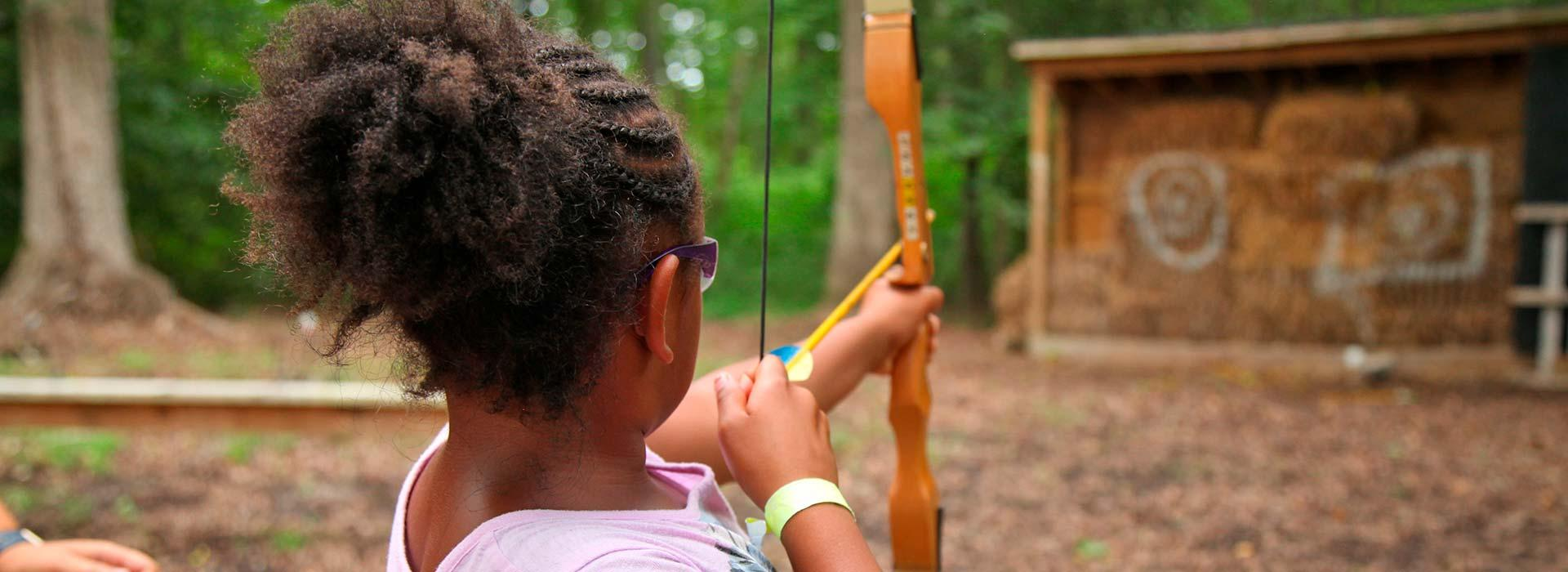 Young girl aiming with bow and arrow at a hay target at YMCA Camp Arrowhead in Suffolk, Virginia