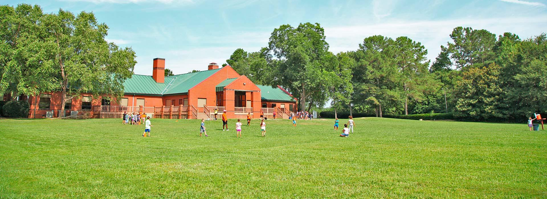 Wide shot of campers playing in field with lodge behind them at YMCA Camp Arrowhead in Suffolk, Virginia