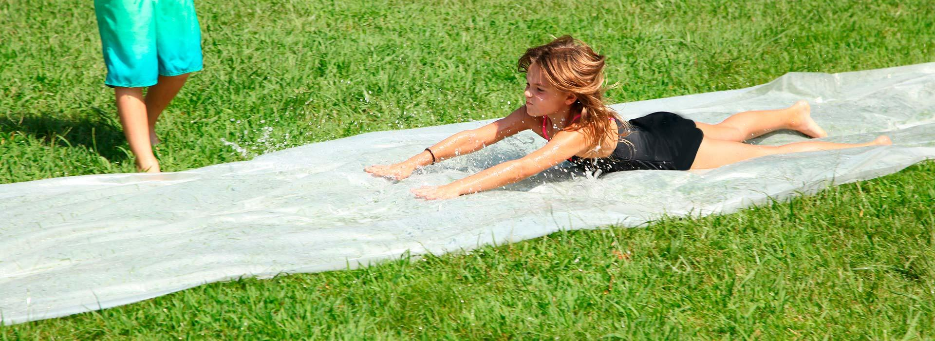 a girl running down a slip and slide
