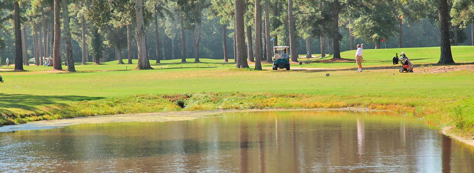 Golf cart and golfer in the background at YMCA of the Pines golf course in Elizabeth City, NC