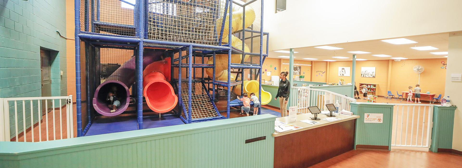 Child care play area including indoor climbing structure with slides