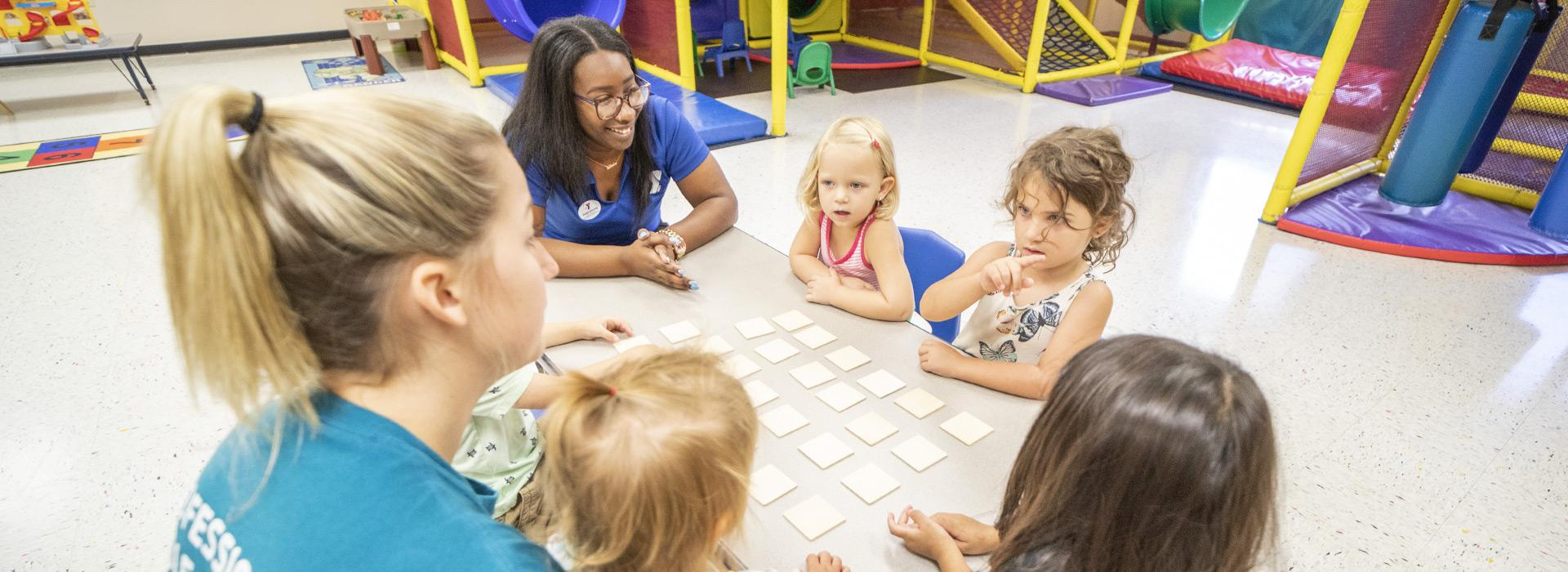 YMCA staff leading a game of memory with preschool aged girls in Stay & Play at the Albemarle Family YMCA