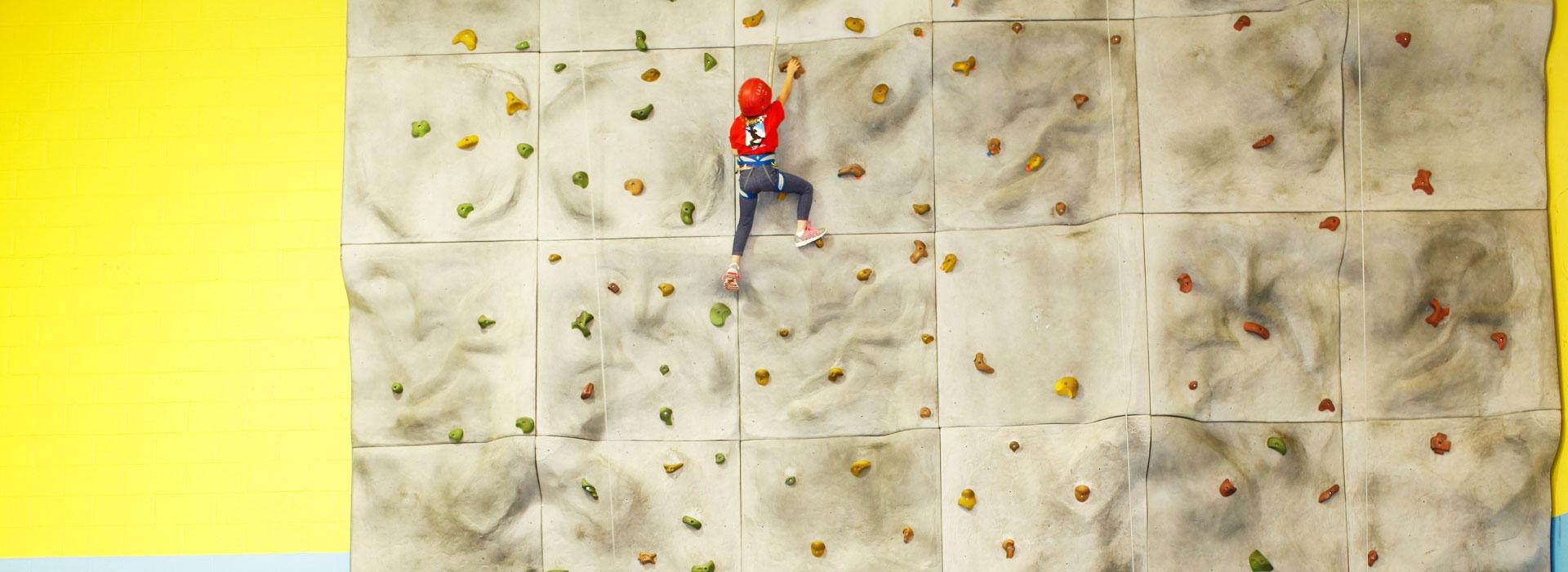 A child in safety harness climbing the rock wall at the Albemarle Family YMCA
