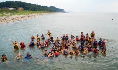 a large group of children at camp swimming in the ocean