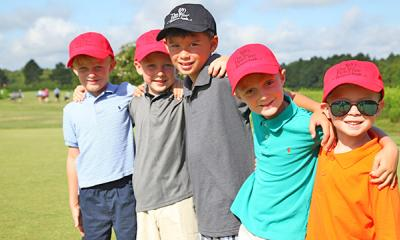 group of boys smiling on golf green
