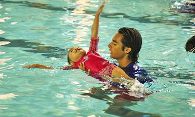 Y employee teaching child how to swim