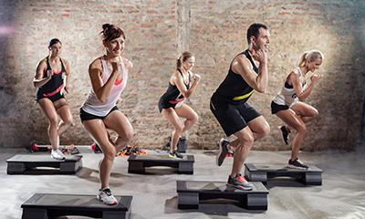 A group of people exercising using cardio steps