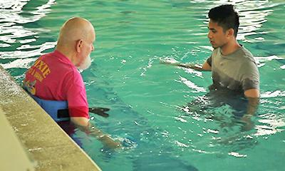 a personal training session in a pool with a senior and trainer